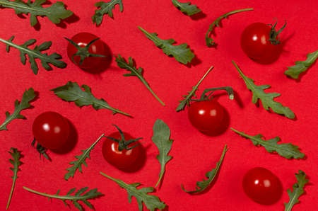 Bright red tomato, green arugula leaves with shadow on red background, top view. Modern food vegetables pattern. 免版税图像