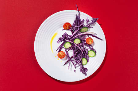 Organic vegetarian salad of vegetable with red cabbage, oil on white plate in sunny day with shadow on red trend color background.