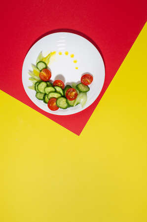 Fresh summer vegetable salad with cherry tomato, cucumber, celery and oil with shadow in sunny day on red and yellow color, top view, vertical. 免版税图像