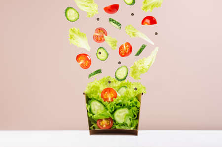 Fresh vegetable salad in craft box for take away food with falling slices of ingredients - cherry tomato, cucumber, green salad on beige background.