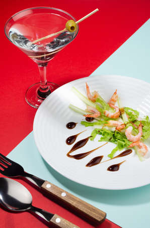 Modern elegant geometric style in food background - lunch of salad with shrimps, greens, celery, teriyaki sauce with martini cocktail with shadow in sunlight on red and mint color, vertical. 免版税图像