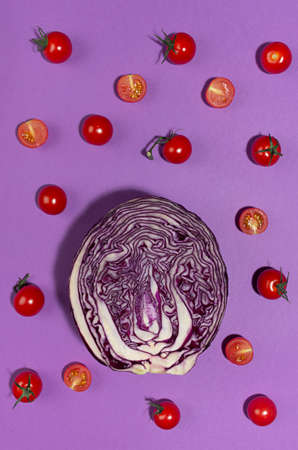 Bright cherry tomatoes and slice red cabbage in hard light with shadow on violet background, flat lay, food colorful pattern.