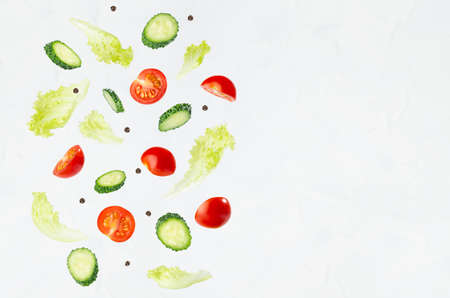 Fresh sliced vegetables for summer salad - cucumber, cherry tomato, green salad - flying on soft light white wall, border, copy space.