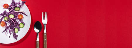 Wellness food - fresh salad of tomato, cucumber, red cabbage, cutlery on white plate in hard light with shadow on red background, banner, top view. 免版税图像