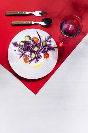Raw healthy salad with purple cabbage, red tomatoes, cucumber, drink in hard light with shadow on modern geometric red color, white wood background, vertical. 免版税图像