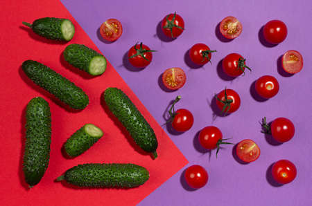 Bright cherry tomatoes, green gherkin cucumber in hard light with shadow on red and violet background, flat lay, food colorful pattern. 免版税图像