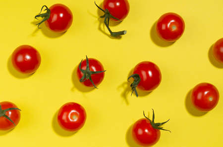 Ripe cherry tomato with shadow on yellow background, top view, food color pattern.