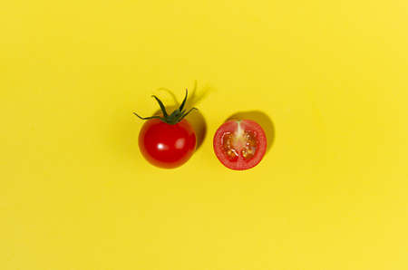 Bright cherry tomato whole and slice in hard light with shadow on yellow background, flat lay, copy space.