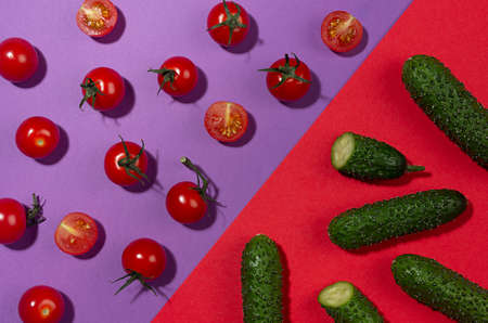 Vegetable colorful abstract pattern - ripe cherry tomato, green young cucumber with shadow whole, sliced on geometric red, purple contrast background, top view.