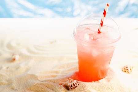Fresh cold strawberry cocktail in transparent misted plastic glass with straw, ice on sunny beach with ocean and white sand, copy space.