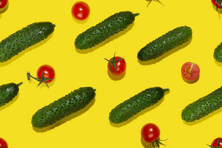 Summer color food seamless pattern - red cherry tomatoes and green gherkin cucumber in sunlight with shadows on yellow backdrop, flat lay.