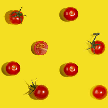 Summer food seamless pattern - red cherry tomatoes whole and sliced in sunlight with shadows on yellow background, flat lay.
