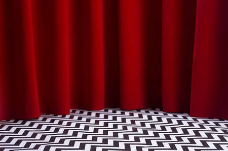 Theater scene with red velvet curtain and black and white tile on floor. Stage for displaying product in twin peaks style.