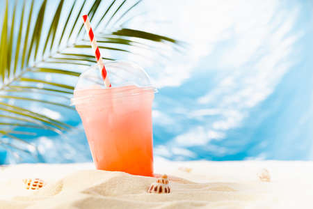 Fresh cold strawberry cocktail in transparent misted plastic glass with straw, ice on sunny beach with palm leaves, ocean and white sand, copy space. 免版税图像