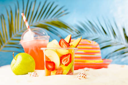 Fresh summer takeaway food on tropical beach - fruit salad, cold drink, green apple, sun hat on white sand with palm leaves in golden sunlight and sea view. Vacation on seaside coast.