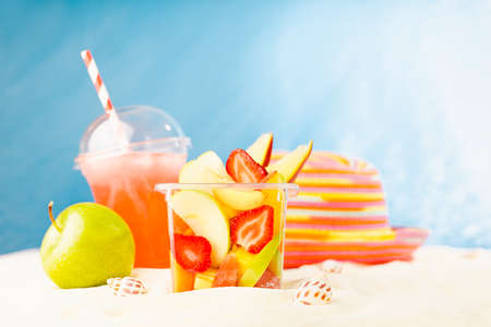 Healthy summer picnic on tropical beach with takeaway fresh food - fruit salad, cold strawberry cocktail, green apple, sun hat on white sand with sunny sea view. Summertime resort. 免版税图像