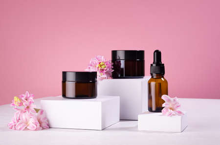 Cosmetic mockup - jars for cream, essential oil bottle of amber glass on white podiums with pink spring flowers. Template for branding identity for cosmetics produce.