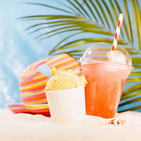 Happiness summer holiday on sunny tropical sea coast under palm with takeaway food and drink - cold juice, ice cream, apple and hat.