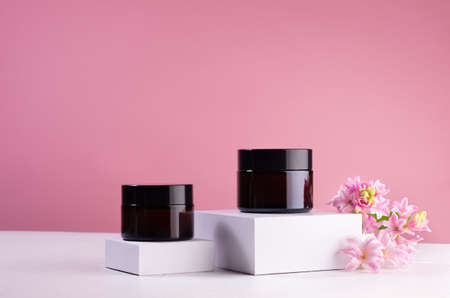 Collection of amber glass containers for cosmetic produce on white podiums with elegant fresh flowers, mockup, copy space.