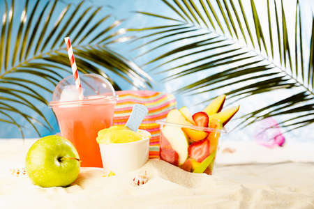 Summer travel, leisure and holiday background - picnic with cold drink, fresh fruit salad takeaway, sun hat, beach plays on hot sunny sandy beach with palm, bright ocean view. 免版税图像
