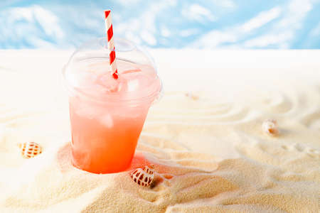 Cold fresh pink fruit drink takeaway with ice cubes on sunny summer beach with sunlight glare, sea. Seaside beach vacation background.
