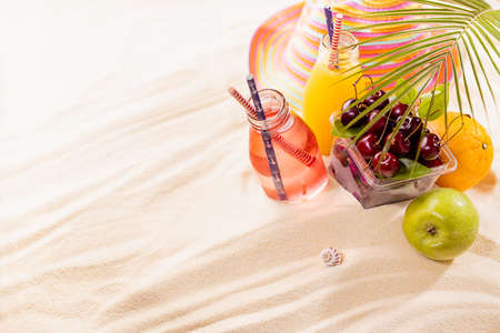 Healthy summer beach vacation on ocean coast - cold juices in glass bottles, fresh cherries, orange, apple, green palm leaf, sun hat in sunlight on sand, copy space. Stock Photo