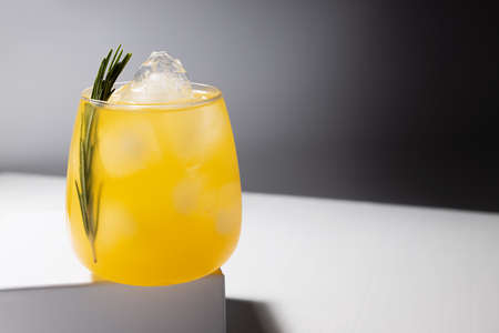 Juicy orange summer beverage with ice, green rosemary twig in glass on pedestal in hard light with dip shadows in abstract modern white bar interior. 免版税图像