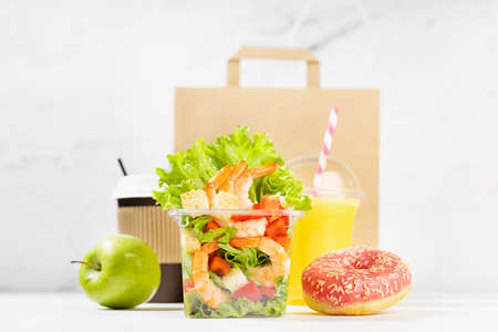 Healthy daily diet plan - set of orange juice, tropical salad with shrimps in plastic box, pink donut, packet in white interior. Advertising for restaurant take away, delivery food service.