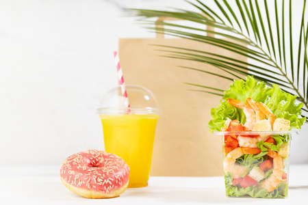 Healthy food set with fresh orange juice, tropical salad in plastic pack, pink donut, packet on in white interior with palm leaf. Concept advertising for restaurant take away or delivery food service.