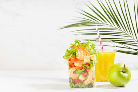 Healthy summer vacation daily diet plan - set of orange juice, green apple, fresh tropical salad with shrimps and vegetables in plastic box in white interior with palm leaf. Organic take away food.