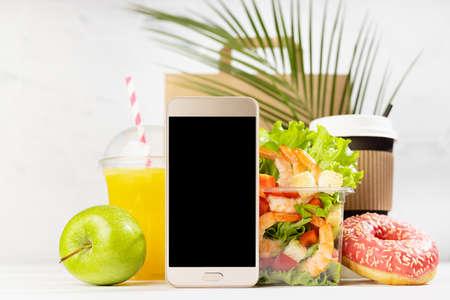 Summer breakfast - drinks, fruit, shrimp salad in plastic pack, donut, packet, black phone in white interior, palm leaf. Mockup advertising for delivery service, take away restaurant, online order.