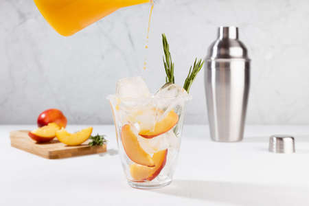 Cooking healthy summer peach juice - cocktail pour of jug in glass with ice, rosemary twig, sugar rim, ingredients in elegant white interior on soft light wood table.