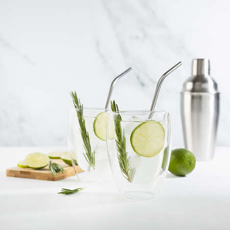 Organic mojito cocktail cooking with citrus fruit slices, ice cubes, green rosemary twig, ingredients, silver shaker, straws, cut board in two transparent mugs on white wood table, marble wall.
