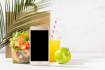 Fitness food set - orange juice, green apple, shrimp salad in box, packet, blank phone in white interior, palm leaf. Mockup advertising for delivery service, take away restaurant, online order.