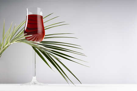 Red porto in luxury high glass decorated elegant curved green palm leaves in hard light with shadow in soft light white abstract interior wooden table, gray wall.