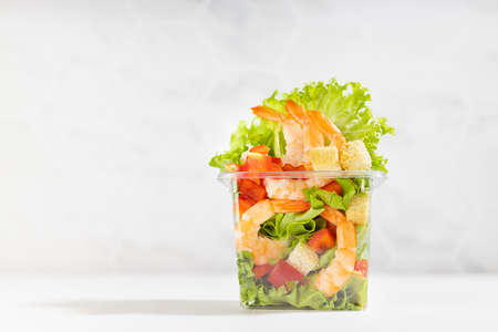 Fresh tropical salad with shrimps, lettuce, red bell pepper, croutons in transparent plastic box on white wood table, marble tile wall. 免版税图像