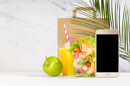 Tropical lunch set of orange juice, sea food shrimp salad in box, blank phone, packet in white restaurant interior, palm leaf. Mockup for advertising for delivery service, take away restaurant.