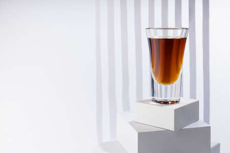Bright amber brandy cocktail in shot glass in sunlight on white square podium as stairs with abstract stripes in soft light space in luxury minimal geometric style.