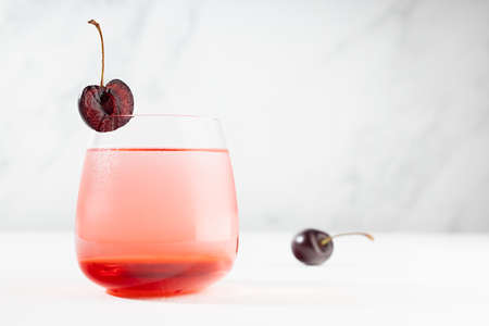 Summer refreshing cold healthy lemonade with cherry syrup, fruit slice in misted glass modern white restaurant interior with marble wall. 免版税图像