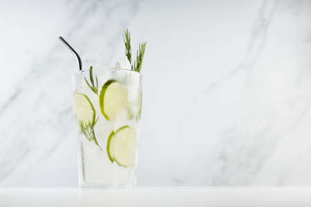 Fresh citrus infused homemade lemonade with ice cubes, lime slices, green rosemary twig, silver straw in soft light white kitchen interior in sunny day.