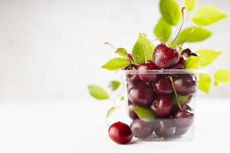 Ripe red cherry with water drops in plastic box with green leaves on white wood board, tile marble wall in modern interior, copy space. 免版税图像