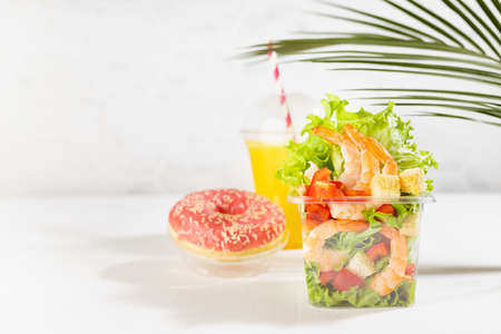 Wellness fresh summer food take away - set of orange juice, pink donut, tropical salad with shrimps, lettuce, red pepper, croutons in plastic box in white bar interior with marble tile, palm leaf. 免版税图像