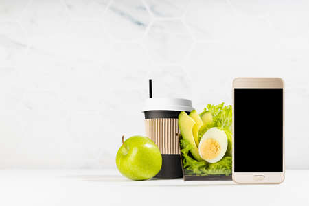 Healthy breakfast take away - set of green salad, cup of coffee, green apple in white interior with blank screen phone. Mockup for advertising for delivery service or take away restaurant. 免版税图像