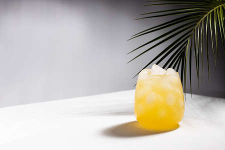 Misted tropical orange juice with ice cubes in glass on podium in sunlight with shadows, palm leaf in white and dark black abstract space or outdoor.