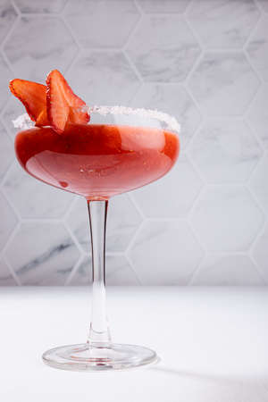 Tropical fresh strawberry juice with pulp in high glass goblet decorated sugar rim, fruit slice in modern white restaurant interior, vertical.