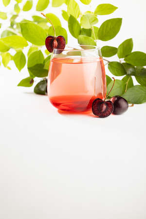 Summer cold layered cherry cocktail with slice cherry, green leaves in gold sunlight on white wood table in soft light white bar interior or garden, vertical. 免版税图像