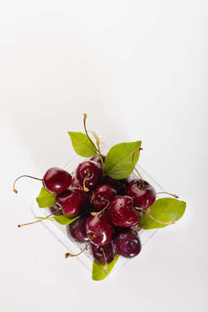 Ripe red fresh wet cherry in plastic box with green leaves, water drops and tail in sunlight on white wood board, top view, copy space, vertical.