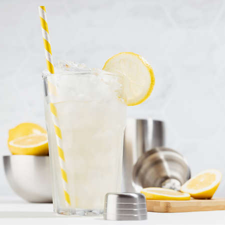 Cold juicy lemon infused cocktail in glass with straw, ice cubes, ingredients in silver bowl, shaker in summer sunlight in soft light white kitchen interior with marble tile, square. 免版税图像