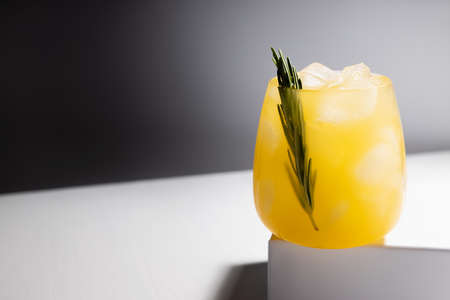 Fresh misted orange alcohol cocktail in glass with ice, green rosemary twig on podium in sunlight with shadows in elegant minimal black and white interior.