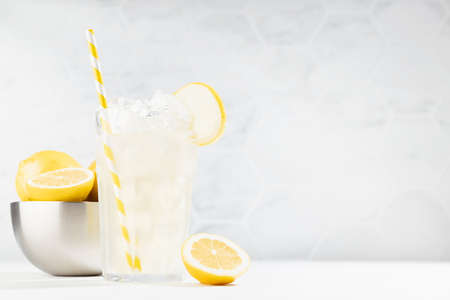 Cold juicy lemon cocktail in glass with straw, ice cubes, yellow lemons in silver bowl in summer sunlight in soft light white kitchen interior with marble tile. 免版税图像